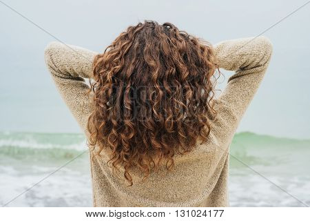 Curly brunette in a sweater on the coast faces the sea and straightens hair view from the back