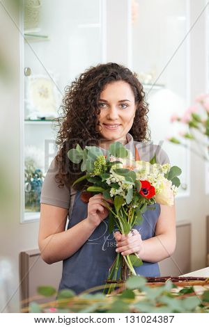 Smiling pretty young woman florist enjoying working in flower shop