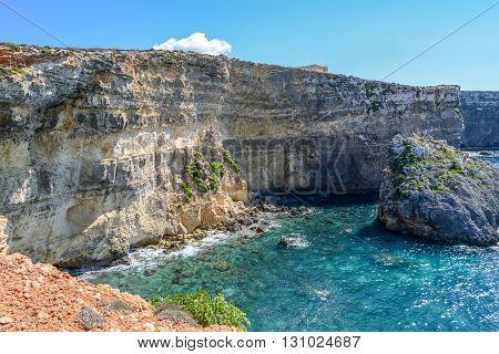 rocky cliffs of Gozo in blue sea near Malta