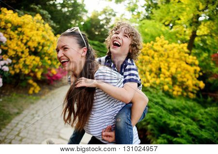 Boy 8-9 years old on the shoulders of a young woman. Both are fun to laugh. They play in a densely flowered garden.