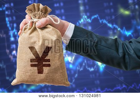 Hand Of Businessman Holds Bag Full Of Money With Yen Sign. Inves