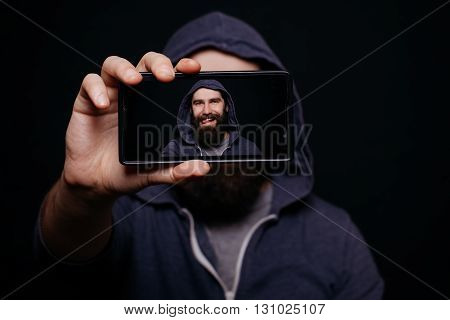 Hipster man with a beard taking picture smartphone self-portrait screen view snapshot studio on a black background