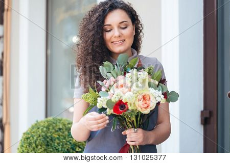 Smiling cute young woman florist with flower bouquet standing in front of shop