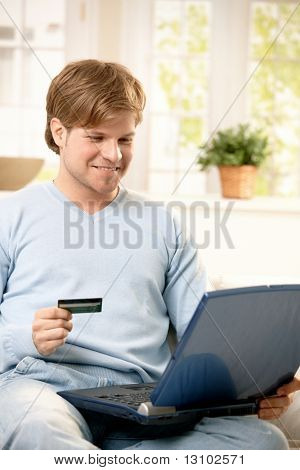 Smiling man shopping online with laptop computer in lap, holding credit card.
