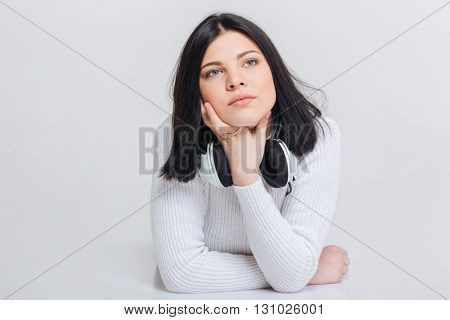 Young beautiful serious brunette woman lying on floor with  headphones isolated on a white background