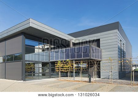 OLDENZAAL, NETHERLANDS - OCTOBER 31, 2015: Modern sustainable office building with solar panels integrated in its facade