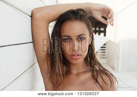 Beauty model with natural nude make up fresh skin and wet hair s posing front of white wall. Youth and Skin Care Concept. Make up and Hair. Close up selected focus.