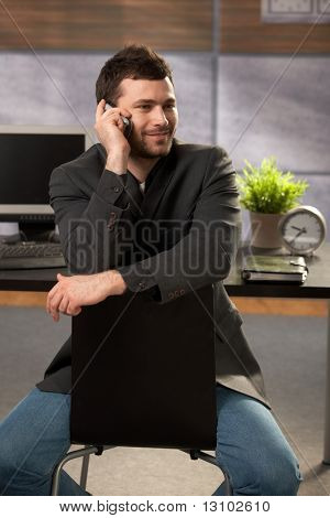 Trendy young businessman sitting on chair in office, talking on mobile phone, smiling.