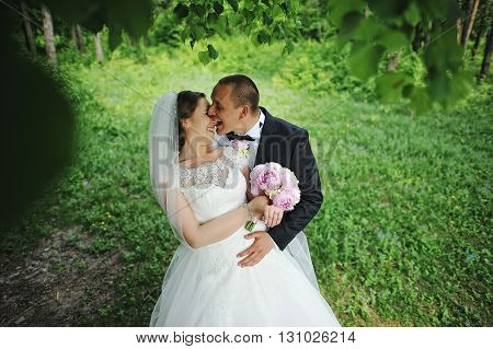 Funny Wedding Couple At Forest, Groom Biting Nose Of Bride