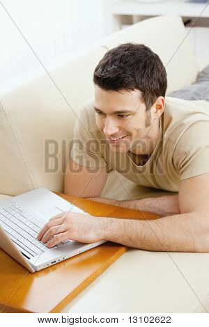 Happy young man laying on sofa at home using laptop computer, smiling.