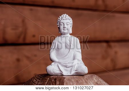 Zen yoga and meditation concept. White Buddha on red wooden relax background.