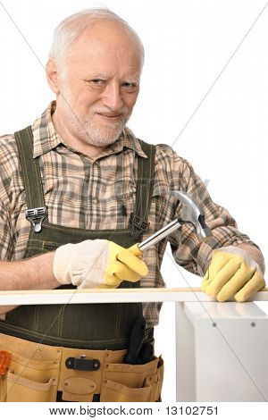 Elderly man hammering, lloking up at camera, smiling, isolated on white.