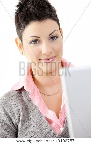 Closeup portrait of young businesswoman, looking at camera, smiling. Isolated on white background.