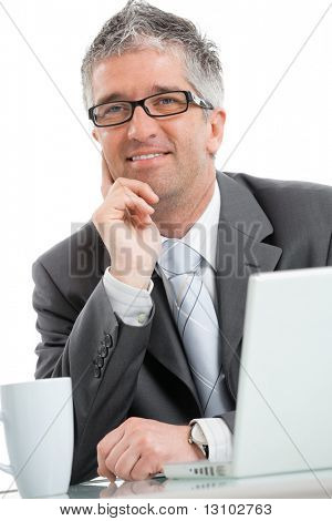 Happy, smiling businessman sitting at office desk working on laptop computer. Isolated on white background.
