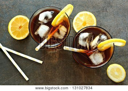 Two Glasses Of Cold Iced Tea With Lemon Slices And Straws, Downward View On Dark Stone Background