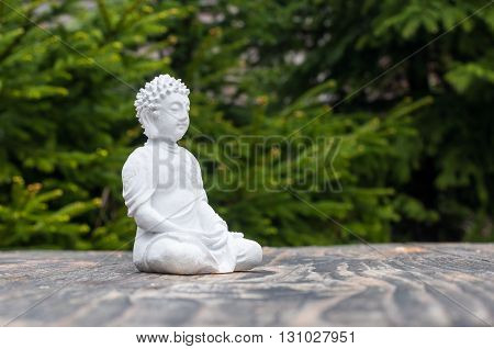 Statue of Buddha - peaceful mind. White deity on blur green background. Meditate concept.