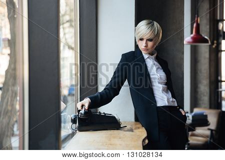 Beautiful stylish blonde girl talking on the phone in cafe
