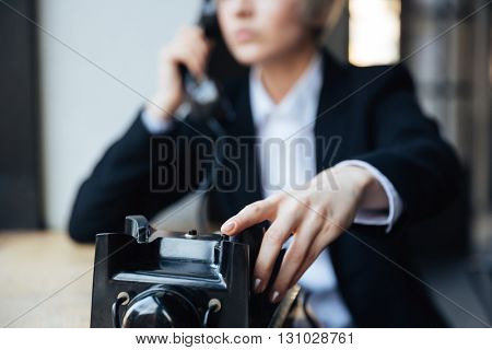 Cropped image of stylish blonde young girl with phone in cafe