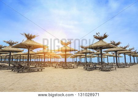 Beach with sun beds and umbrellas at sunset.