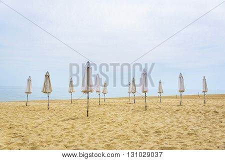 Folded umbrella on beach. Vacation concept seasonal period.