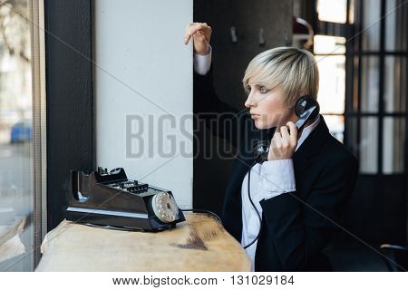 Blonde stylish girl using old fashioned telephone in cafe