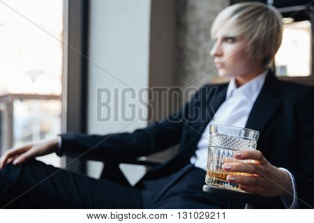 Stylish pretty blonde girl holding glass of alcohol drink and sitting in cafe