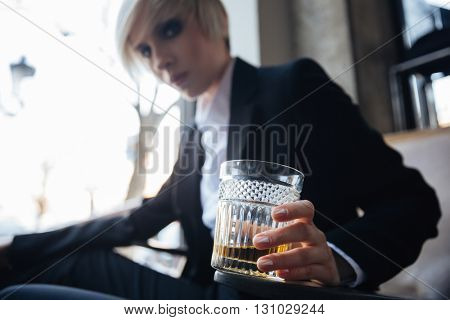 Young attractive blonde girl with frustrated and displeased look holding glass