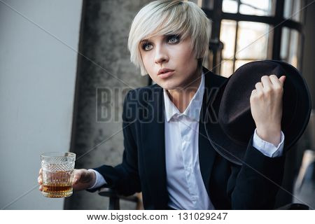 Beautiful blonde girl drinking and holding hat in cafe