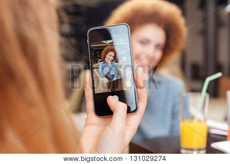 Female holding smartphone and taking pictures of cheerful beautiful redhead young woman sitting in cafe
