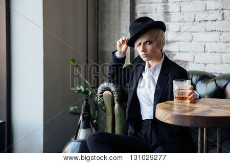 Pretty blonde girl sitting on the couch in a hat with her legs crossed and holding a glass