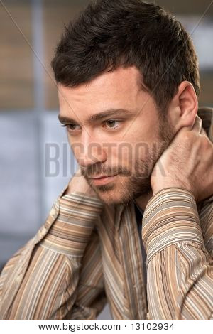 Young handsome man sitting with hands on neck looking thoughtful and concentrating.