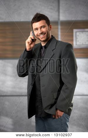 Portrait of happy businessman talking on cellphone standing in office, smiling.