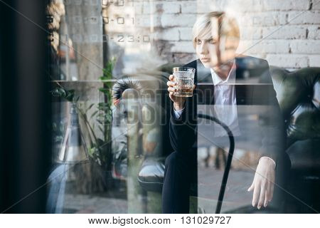 Stylish pretty blonde girl holding a glass of alcohol drink in a cafe, street reflection in window