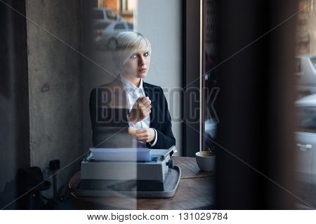Stylish pretty blonde girl waiting for someone in a modern cafe,street reflection in window