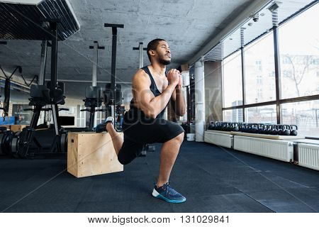 Muscular fitness man doing squats using wooden stand in the gym