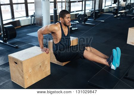 Strong fitness man pumps biceps using training apparatus in the gym