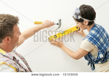 Couple working together on home renovation, woman holding spirit level tool, man holding hammer.