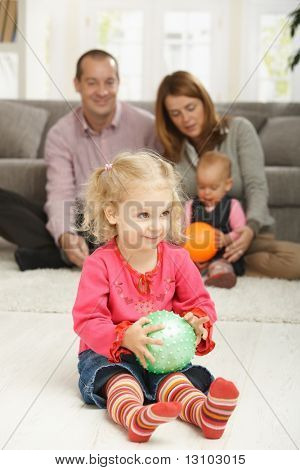 Smiling toddler holding ball with parents and baby in background.