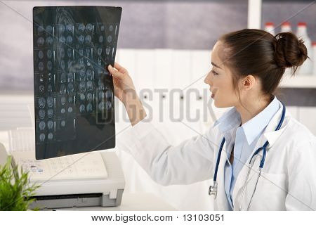 Young female doctor sitting at desk in doctor's room looking at x-ray image.