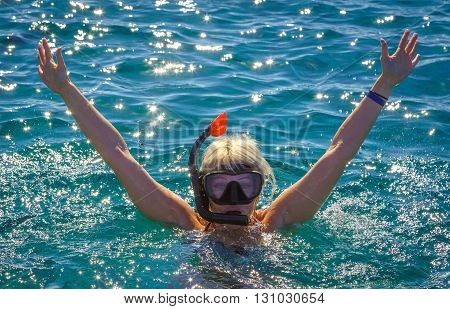 Girl in the sea in a mask for diving