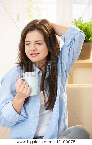 Young woman sitting on sunlit living room sofa holding tea cup, smiling.
