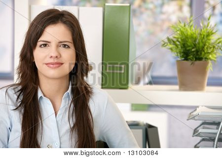 Portrait of pretty young woman sitting in office.