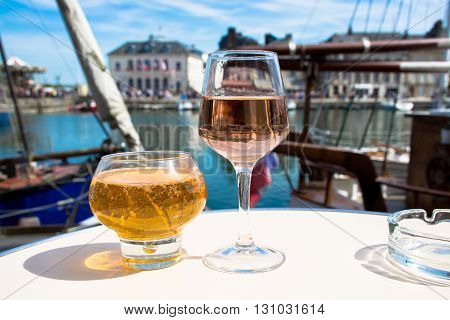 Normandy apple cider in traditional glass and rose vine in old French fisherman village