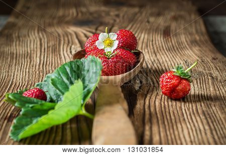 Fresh red strawberries in wooden spoon on wooden background. Macro selective focus.