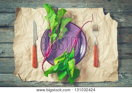 Two fresh beetroots on purple plate with battered craft paper as a background. Served with fork and knife. Top view toned.