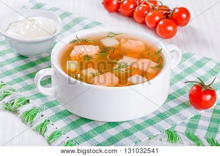 salmon soup with vegetables and dill in a white bowl on a table cloth on an rustic tableview from above close-up