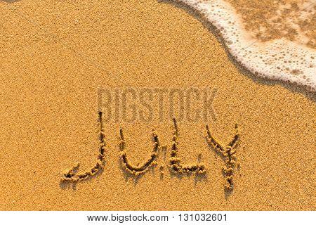 July - written by hand on a golden beach sand.