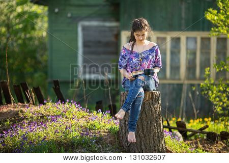 Teen girl reads book sitting on a stump in the yard in the village.