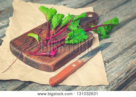 Sliced beet root on old rustic cutting board and wooden background. Selective focus toned.