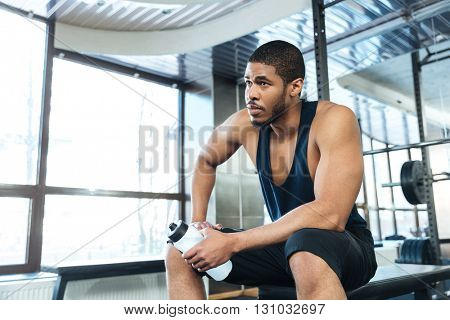 Afro american fitness man resting on the bench in the gym